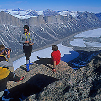 Mountaineer Jared Ogden photographs Mark Synnott and Alex Lowe atop Great Sail Peak, high above the spectacular Steward Valley, north of the Arctic Circle on Canada's Baffin Island.