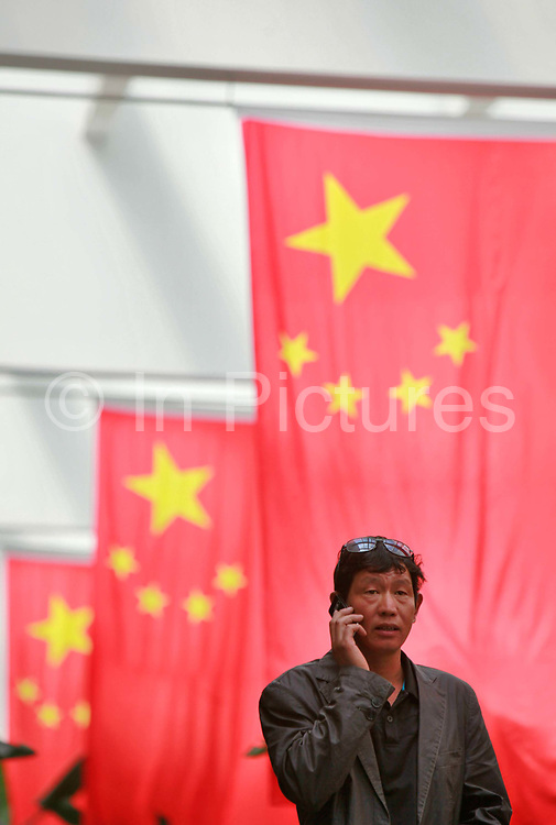 A man Chats on his cellphone while standing under Chinese national flags in Shanghai, China, on October 04, 2011. While China's mobile phone subscribers is expected to reach 1 billion by the end of March, 2012; the world's largest mobile communications is however effectively monlopolized and strategically controlled by the Chinese government through giant state champions such as China Mobile, China Unicom, and China Telecom.