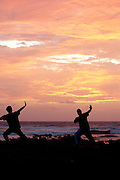 Two men face the east on the shore of Kauai to stretch to the rising sun.