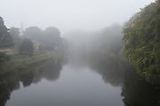 Seen from the 14th century Warworth old Bridge, a landscape of the river Coquet on a misty autumnal morning on 26th September 2017, in Warkworth, Northumberland, England. Warkworth is a village in Northumberland, England. It is probably best known for its well-preserved medieval castle, church and hermitage. The River Coquet runs through the county of Northumberland, England, discharging into the North Sea on the east coast of England at Amble. Warkworth Castle is built in a loop of the Coquet.