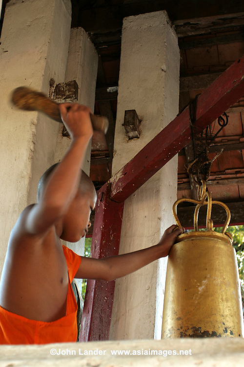 Novice Ringing the Temple Bell -  The type of Buddhism practiced in Laos is a unique version of Theravada Buddhism which is at the basis of Lao culture. Buddhism in Laos is often tied to animist beliefs and in ancestral spirits.  It is usual for most Lao boys to go into a temple for a period of time, usually a month or six weeks at least, before adulthood.