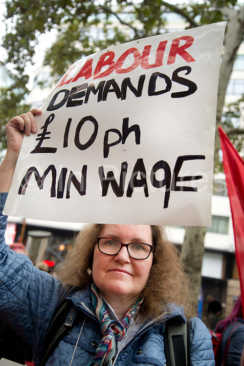 Food service industry workers strike for higher wages on October 4th 2018 in Leicester Square, London, United Kingdom. Day of action by workers from TGI Fridays, McDonalds; Deliveroo and Wetherspoons, supported by TUC and Labour Party, demanding better conditions for the hospitality sector. A woman holds a placard saying Labour demands £10 per hour minumum wage.