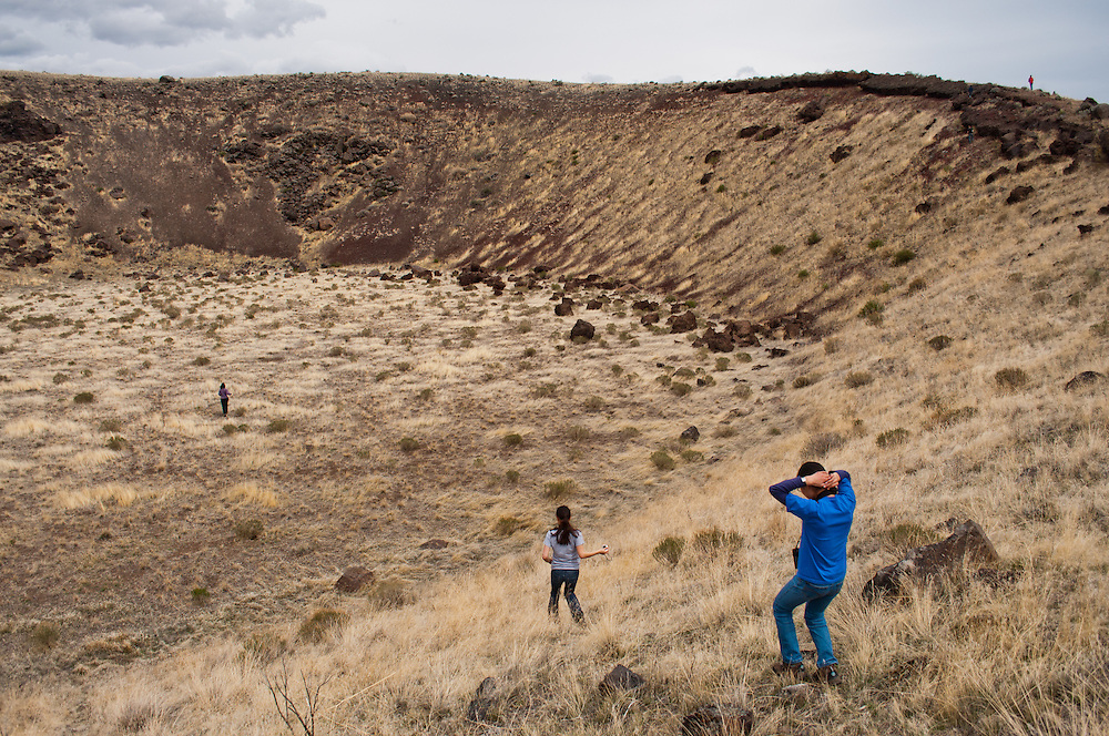 People exploring a volcano crater at the Diamond Craters Outstanding Natural Area, Oregon.