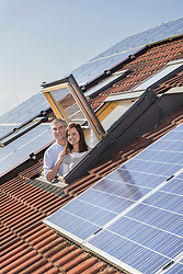 Couple looking out from roof window with solar panels