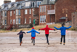 Pictured: Santa Beach Run on the scenic East Lothian coast. This new event is aimed at athletes, casual runners and families. It is hosted by Project Trust with proceeds enabling local school leavers to spend a year volunteering in India/Honduras to teach at a school with few teaching materials. Children limber up before their 2km race. 15 December 2018  <br /> <br /> Sally Anderson | EdinburghElitemedia.co.uk