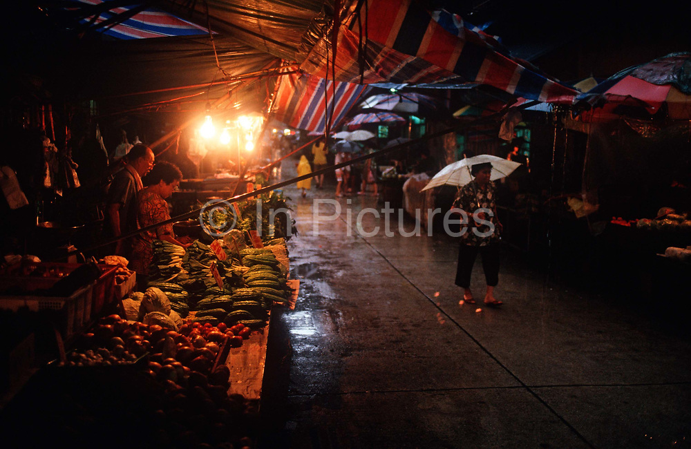 While still a Portuguese colony, 1990s monsoonal rain falls heavily in a Macau market of vegetable stalls, on 10th August 1994, in Macau, China.