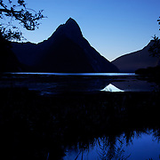 Mitre Peak at sunset. Mitre Peak is an iconic mountain in the South Island of New Zealand. It is one of the most photographed peaks in the country. Part of the reason for its iconic status is its location. Close to the shore of Milford Sound, in the Fiordland National Park in the southwestern South Island, it is a stunning sight. Rising to 1,692 metres from the water of the sound. it is actually a closely grouped set of five peaks, although from most easily accessible viewpoints it appears as a single point. Milford Sound,  Milford Sound, New Zealand. 29th April 2011. Photo Tim Clayton