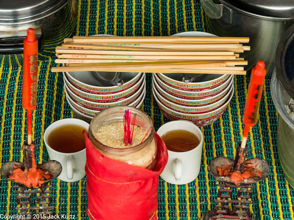 28 AUGUST 2015 - BANGKOK, THAILAND: Bowls, chopsticks and tea left out for ghosts on Hungry Ghost Day in Bangkok's Chinatown. Mahayana  Buddhists believe that the gates of hell are opened on the full moon of the seventh lunar month of the Chinese calendar, and the spirits of hungry ghosts allowed to roam the earth. These ghosts need food and merit to find their way back to their own. People help by offering food, paper money, candles and flowers, making merit of their own in the process. Hungry Ghost Day is observed in communities with a large ethnic Chinese population, like Bangkok's Chinatown.     PHOTO BY JACK KURTZ