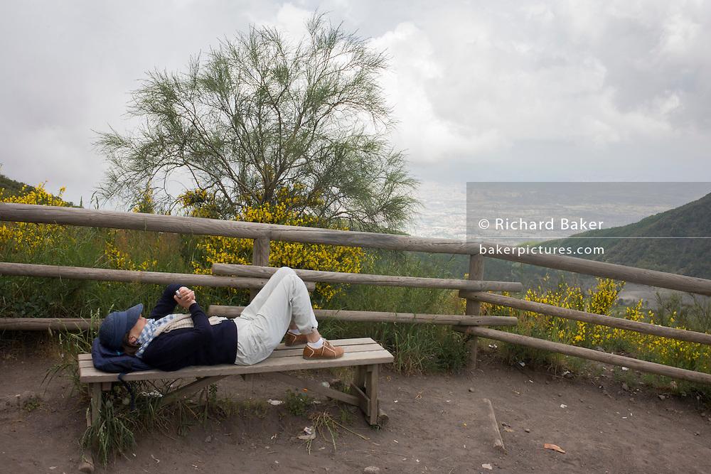 Man checks smartphone during visit to the Vesuvius volcano.
