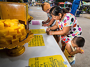 20 JULY 2015 - NONTHABURI, NONTHABURI, THAILAND: A woman inscribes a prayer on to a piece of wax while her son prays on Nonthaburi Pier, the end of the Chao Phraya Express Boat line in Nonthaburi, a suburb of Bangkok. This is the north end of a plan to develop the Chao Phraya River riverfront. The Chao Phraya promenade is development project of parks, walkways and recreational areas on the Chao Phraya River between Pin Klao and Phra Nang Klao Bridges. The 14 kilometer long promenade will cost approximately 14 billion Baht (407 million US Dollars). The project involves the forced eviction of more than 200 communities of people who live along the river, a dozen riverfront  temples, several schools, and privately-owned piers on both sides of the Chao Phraya River. Construction is scheduled on the project is scheduled to start in early 2016. There has been very little public input on the planned redevelopment.          PHOTO BY JACK KURTZ