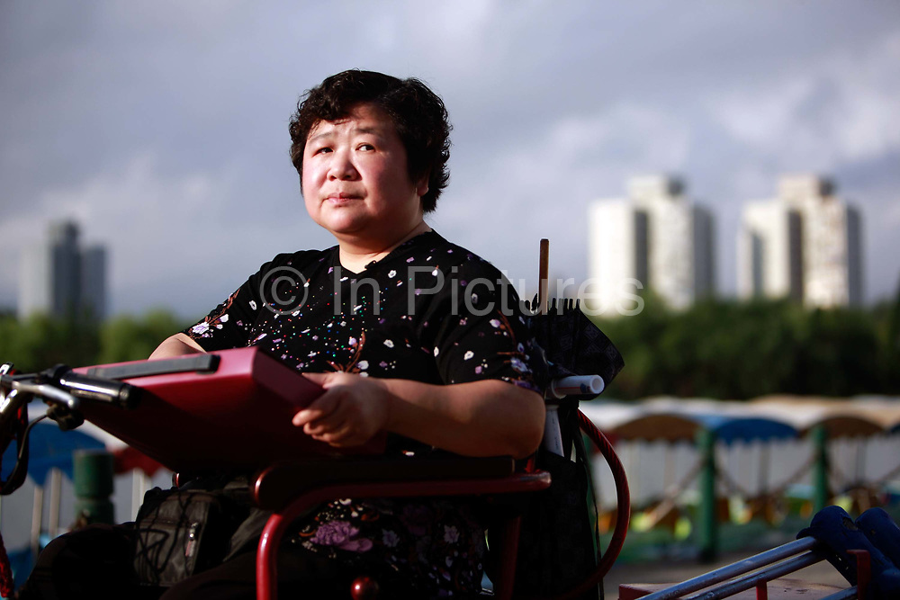Lu Yafang, an investor who claimed that she lost her life saving of 100,000 RMB (roughly 15,500 USD) to investment schemes promoted by the local government, photographed in Shanghai, China on 04 August, 2011. With the banking interest rate artificially depressed by the Chinese government, the average Chinese citizen has little option to increase their wealth in the face of inflation, causing some of them to put their money in risky and often fraudulent schemes.