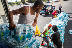 Food Lion employee Dell Locklear, foreground, helps offload pallets of free bottled water for residents of Lumberton, NC, USA, after Hurricane Matthew caused downed trees, power outages and massive flooding along the Lumber River, on Wednesday, October 12, 2016. Photo by Travis Long/Raleigh News & Observer/TNS/ABACAPRESS.COM