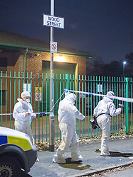 © Licensed to London News Pictures . 31/10/2014 . Manchester , UK . Police and forensic examiners on Wood Street in Openshaw , East Manchester this evening (Friday 31st October 2014) as Greater Manchester Police launch a murder investigation after a man was fatally shot . Armed police from GMP responded to a call at Manchester Food Traders on Wood Street , Openshaw this evening (Friday 31st October 2014) and discovered the man , believed to be 35 years old , injured by two gunshot wounds , one to his abdomen and another to his chest . The man was taken to hospital but died . Photo credit : Joel Goodman/LNP