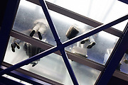 "Looking up through a transparent floor, we see motionless passengers standing and waiting for a lift to arrive at Heathrow Airport's Terminal 5 'Heathrow Express' train link to central London. With their possessions of wheelie bags and a trolley laden wuth luggage, the unseen peoples' feet make a hard impression on the flooring with strong diagonal lines of this industrial design by architects HOK International in conjunction with Rogers, Stirk, Harbour & Partners. From writer Alain de Botton's book project ""A Week at the Airport: A Heathrow Diary"" (2009)."