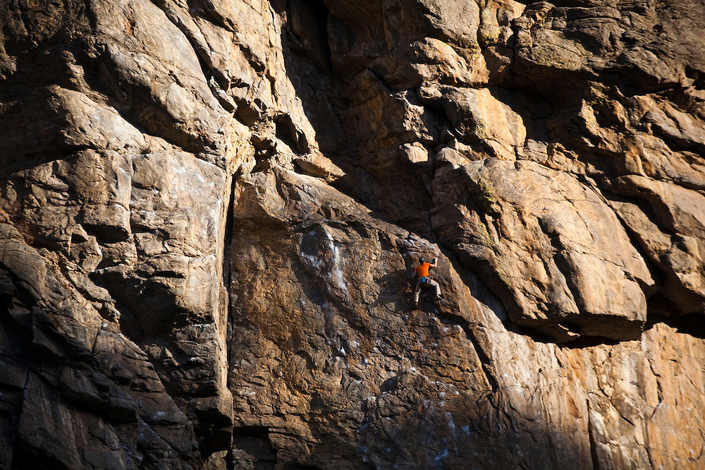 A young man rock climbs in Clear Creek Canyon, Colorado.