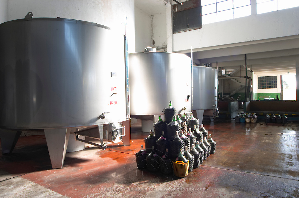 Steel fermentation tanks and glass demijohns in plastic baskets in the winery with a ray of sunshine. Bodega Plaza Vidiella Winery, Las Brujas, Canelones, Uruguay, South America