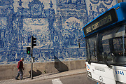 An elderly gentleman walks uphill on the Rua de Fernandes Tomas where a bus has stopped at lights and Azulejo tiles are seen on the exterior of Capela Das Almas, on 19th July, in Porto, Portugal. The Churchs magnificent panels depict scenes from the lives of various saints, including the death of St Francis and the martyrdom of St Catherine. Eduardo Leite painted the tiles in a classic 18th-century style, though they actually date back only to the early 20th century.