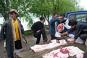 Buying and selling meat from the back of a van at Lugu Lake, Yunnan, China. Lugu Lake is located in the North West Yunnan plateau in the centre of Ninglang Yi Autonomous County in the Peoples Republic of China.
