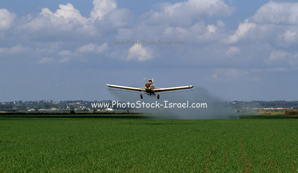 Crop dusting An airplane spraying insecticide over crops. Photographed in Jezreel Valley, Israel