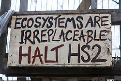 A sign calling for a halt to the destruction of irreplaceable ecosystems for the HS2 high-speed rail link is pictured outside Stop HS2's Wendover Active Resistance Camp on 9th April 2021 in Wendover, United Kingdom. Tree felling work for the project is now taking place at several locations between Great Missenden and Wendover in the Chilterns AONB, including directly opposite the camp.