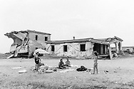 People sunbath nearby abusive houses on the beach of Castel Volturno, southern Italy, on July 21, 2013.