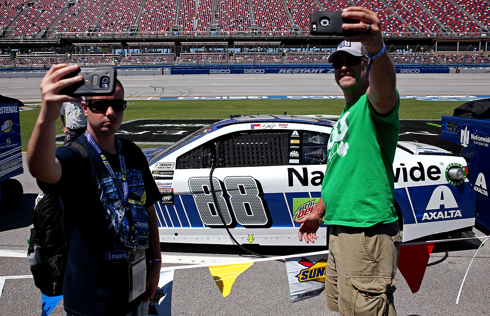 May 7, 2017; Talladega, AL, USA; Fans pose for pictures with the car of NASCAR Cup Series driver Dale Earnhardt Jr. (88) before the GEICO 500 at Talladega Superspeedway. Mandatory Credit: Peter Casey-USA TODAY Sports