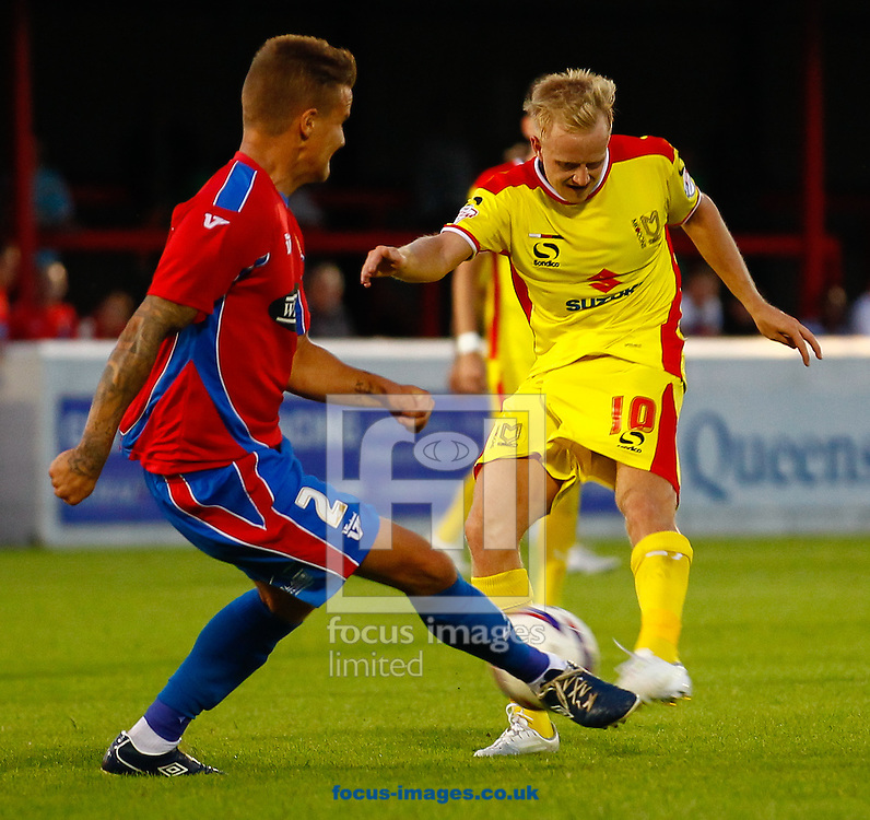 Matt Partridge of Dagenham and Redbridge tries to block a shot from ;Ben Reeves of Milton Keynes Dons during the Pre Season Friendly match at the London Borough of Barking and Dagenham Stadium, London<br /> Picture by David Horn/Focus Images Ltd +44 7545 970036<br /> 22/07/2014