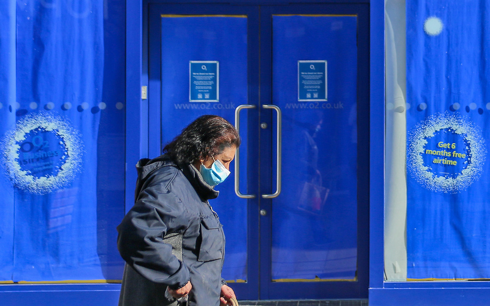 27th February, Cheltenham, England. A woman walks past O2 wearing a mask during the third national lockdown.