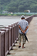 Asia, Southeast, People's Republic of China, Hong Kong, The pier at Tai O man strolling with an umbrella