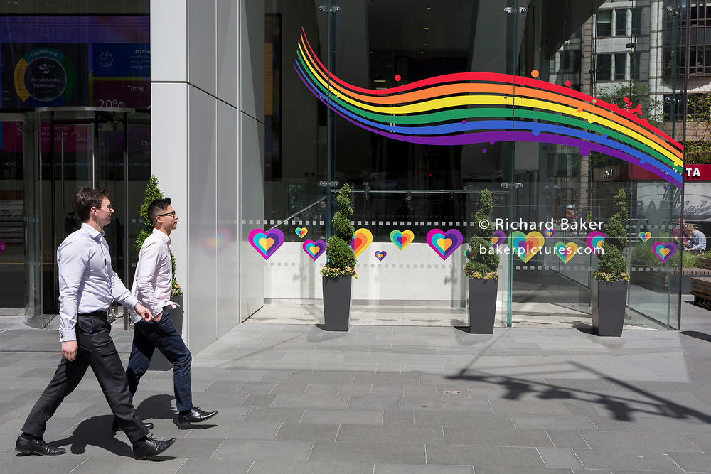 At lunchtime, businessmen in their shirts walk past a window featuring a rainbow and hearts for the Insurance brand Aviva in the City of London, the capital's financial district, on 17th June 2019, in London, England.