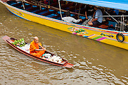 "10 JULY 2011 - AMPHAWA, SAMUT SONGKRAM, THAILAND:    A Buddhist monk from Wat Amphawan Chetiyaram in Amphawa, Thailand, about 90 minutes south of Bangkok, paddles past a water taxi down the main canal during his alms round. Most of the monks from the temple use boats to go from house to house on their alms rounds. The Thai countryside south of Bangkok is crisscrossed with canals, some large enough to accommodate small commercial boats and small barges, some barely large enough for a small canoe. People who live near the canals use them for everything from domestic water to transportation and fishing. Some, like the canals in Amphawa and nearby Damnoensaduak (also spelled Damnoen Saduak) are also relatively famous for their ""floating markets"" where vendors set up their canoes and boats as floating shops.     PHOTO BY JACK KURTZ"