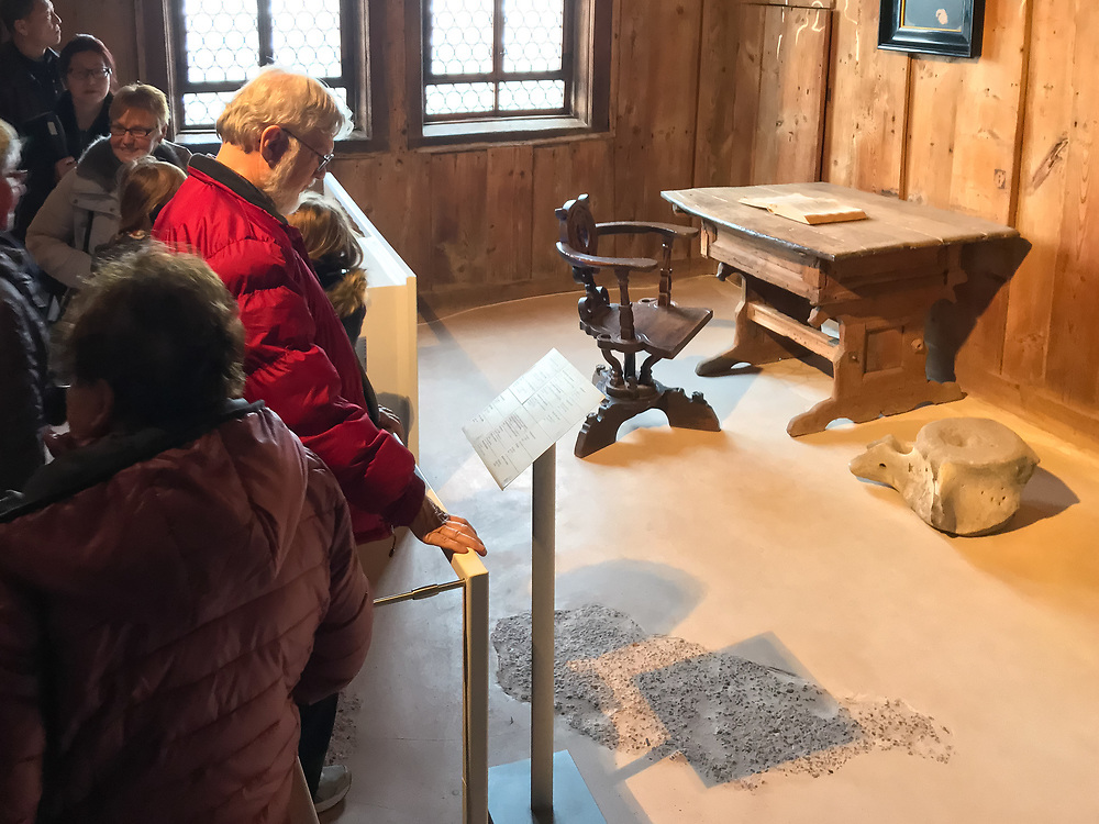 Bruce Wachholz '58, in the red coat, stands in the Wartburg Castle room Martin Luther stayed at while translating the Bible to German.