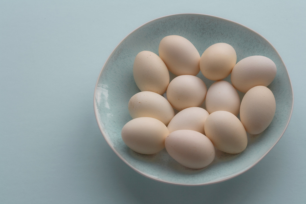 White eggs on a blue bowl on a blue background.