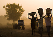 Women carry water buckets on their heads as they walk back home from Dikunani dam in Savelugu, northern Ghana, on Friday March 9, 2007. The only of four water sources that has not completely dried out around Savelugu, the pond is used by hundreds of people daily who sometimes walk several kilometers to fetch water. Despite the presence of mesh filters available to people who come get water, cases of guinea worm in the area have gone up sharply in the recent months.