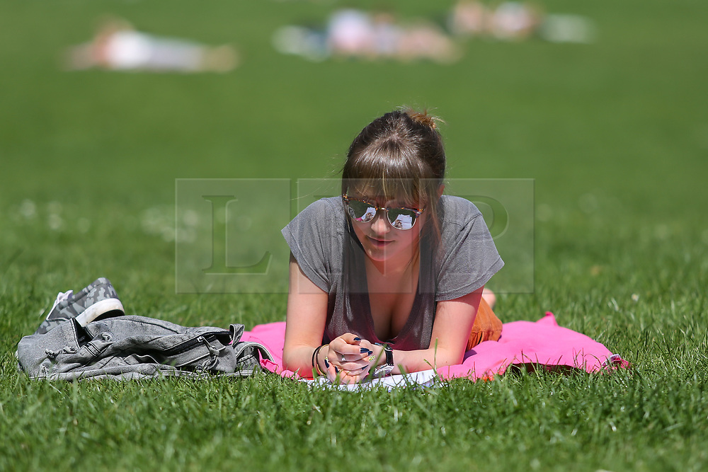 © Licensed to London News Pictures. 25/05/2017. Leeds, UK. A woman bathes in the bright sunshine and warm weather in Hyde park in Leeds, West Yorkshire. Forecasters are predicting the temperatures to rise further still over the bank holiday weekend. Photo credit : Ian Hinchliffe/LNP
