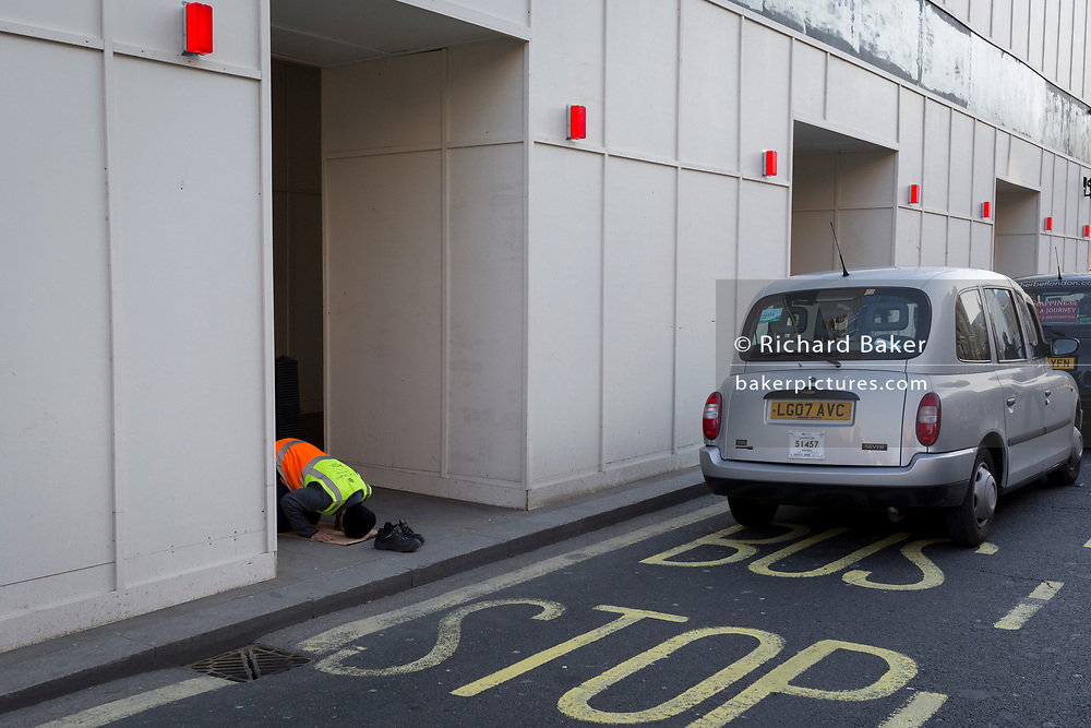A Muslim man, a contract street cleaner, prays near a line of taxi cabs during a cab drivers' protest, in Whitehall, on 15th February 2019, in Westminster, London, England.