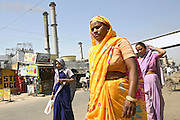 Women are walking on a road by the Khatauli Sugar Mill, (visible in the background) one of the biggest sugarcane mills in Asia, run by Triveni Engineering, located in the city of Khatauli, pop. 10000, Muzaffarnagar District, Uttar Pradesh, India, on Sunday, apr. 20, 2008.