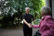 Catholic priest bids goodbye to parishioner after morning Mass at St. Lawrence's Catholic church in Feltham, London.