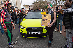 """© Licensed to London News Pictures;21/03/2021; Bristol, UK. A car is temporarily trapped in the crowd at a """"Kill the Bill"""" protest against Police, Crime, Sentencing and Courts Bill takes place through the centre of Bristol during the Covid-19 coronavirus pandemic in England. The Bill proposes new restrictions on protests. Lockdown restrictions have been partly lifted to allow people to gather outdoors socially in households, bubbles, or to meet one person from another household, but the police say protests are not allowed under the current Covid regulations. Photo credit: Simon Chapman/LNP."""