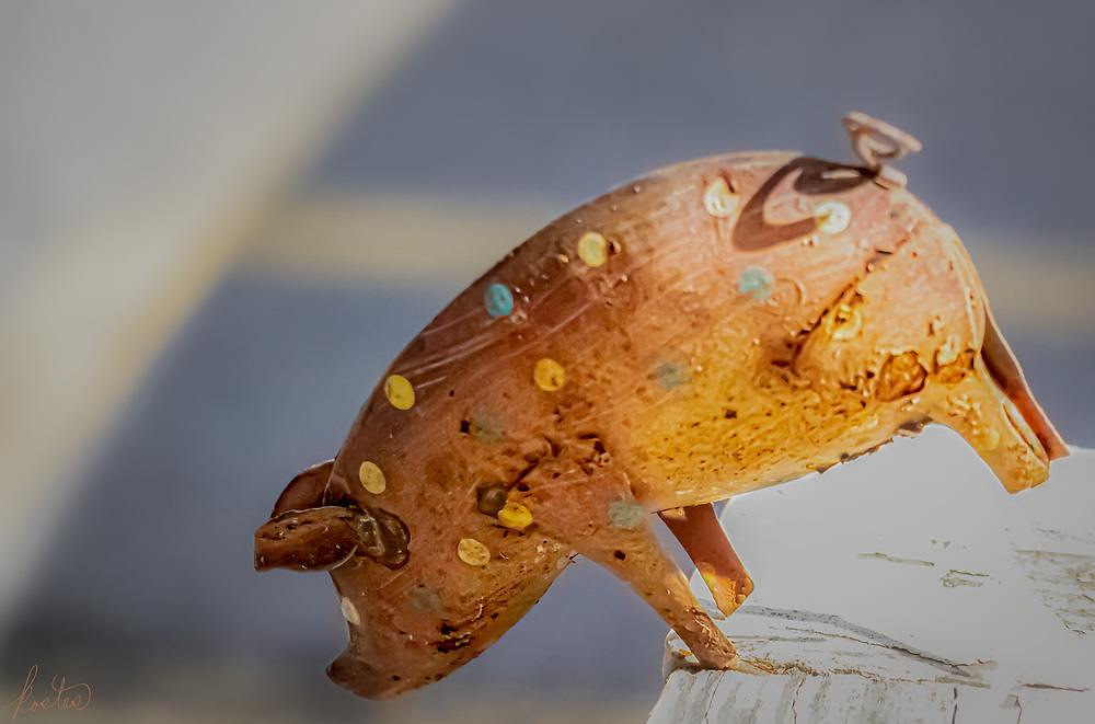 Small metal pig sculpture, leaping off railing.