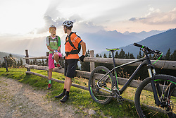 Young couple of mountain bikers standing by wooden fence during sunset, Zillertal, Tyrol, Austria