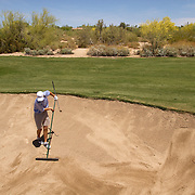 Jordan Spieth rakes his own sand trap, something a caddie would typically handle, but there are no caddies on the AJGA.