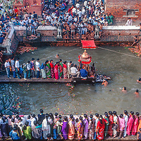 Hindu celebrants gather around Kumbeshwar Temple, in Patan, Nepal, where higher caste men bathe and change their sacred threads & women line up for darshan blessings.