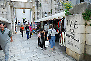 Graffiti on wall, woman and two children shopping at outdoor market. Silver (Eastern) Gates, Diocletian Palace, Split, Croatia