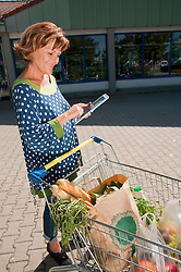 Senior woman using digital tablet with shopping cart