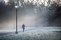 © Licensed to London News Pictures. 22/01/2021. London, UK. A woman walks through a frost and mist covered landscape in Hyde Park, central London on a cold winter morning. Parts of the UK are currently experiencing heavy flooding caused by heavy rainfall during storm Christoph.  Photo credit: Ben Cawthra/LNP