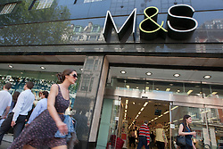 © licensed to London News Pictures. London, UK 22/05/2012. A shopper going past a Marks & Spencer store in Oxford Street as M&S reported a 16 percent fall in full-year net profit today (22/05/12). Photo credit: Tolga Akmen/LNP