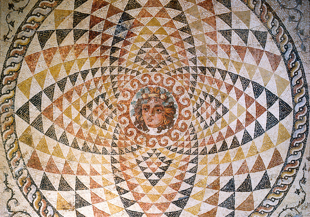This mosaic floor of Dionysos framed by ornaments comes from a Roman villa built in the 2nd century A.D. in Ancient Corinth, Greece.