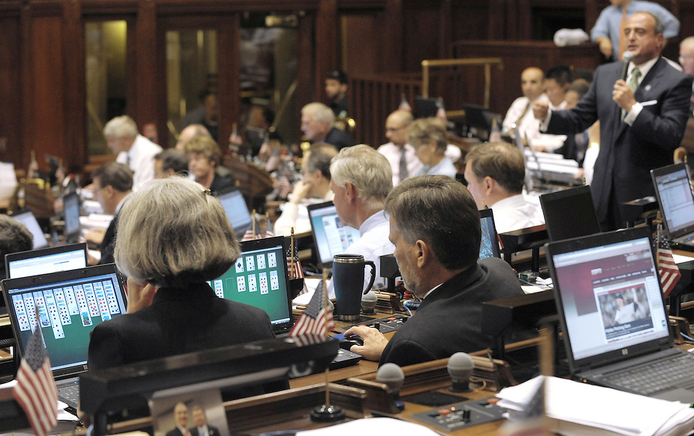 House Minority Leader Lawrence F. Cafero Jr., R-Norwalk, far right, speaks while colleagues play solitaire on their computers as the House convenes to vote on a new budget for the fiscal year in the Capitol, in Hartford, Conn.