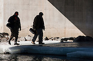 Two men walk on ice underneath a bridge after fishing   in the Neversink River in Cuddebackville, New York, on the opening day of trout season in New York State.